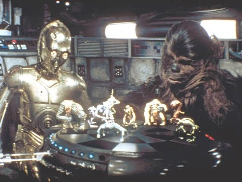 Star Wars has about a million gadgets I want, but the one that always sticks out the most is the holographic wrestling game on they have on the Millennium Falcon. All the little characters looked great, and the idea of a truly three-dimensional playing fi
